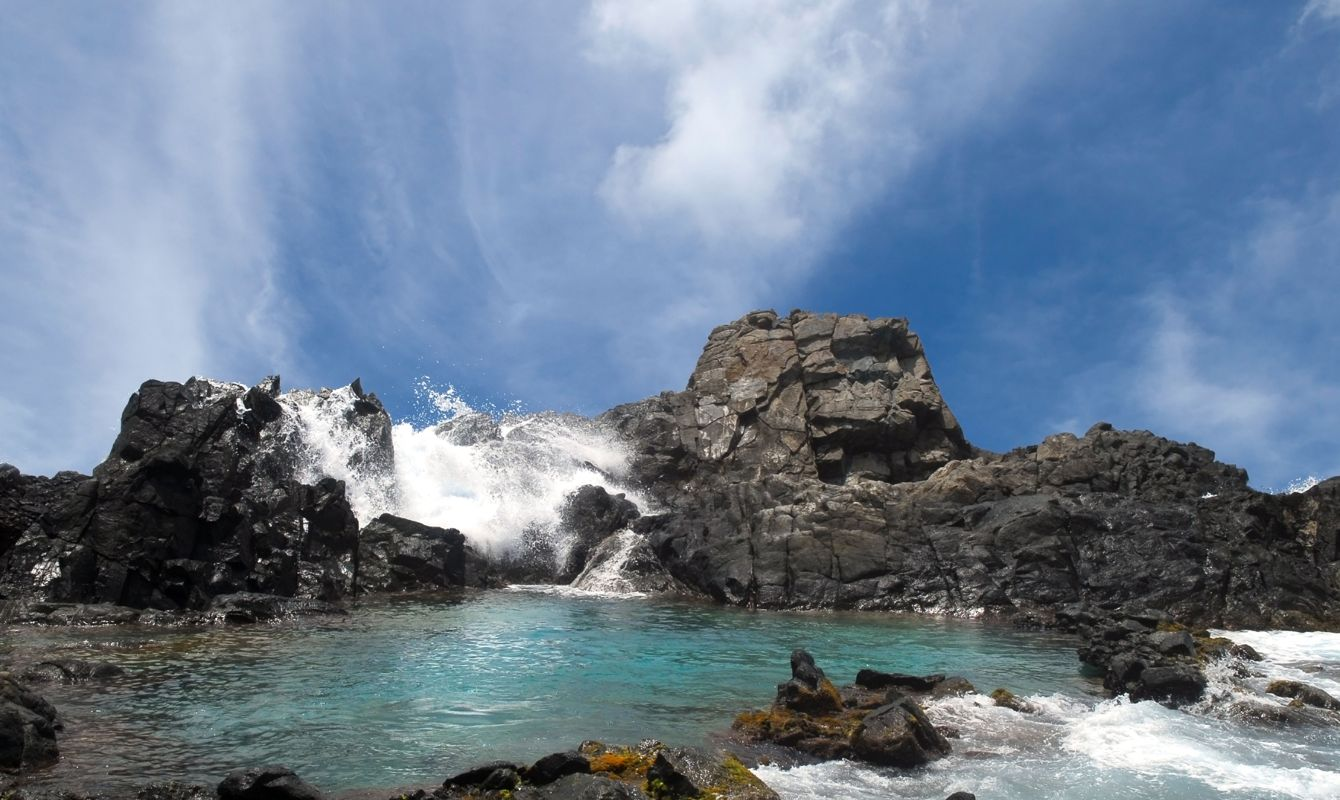Waves crashing over the rocks surrounding the Natural Pool in Aruba