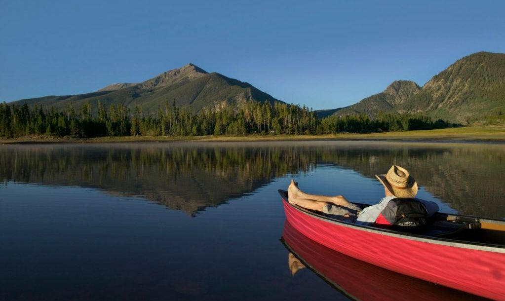 Man Relaxing in Canoe and Looking at Mountain View