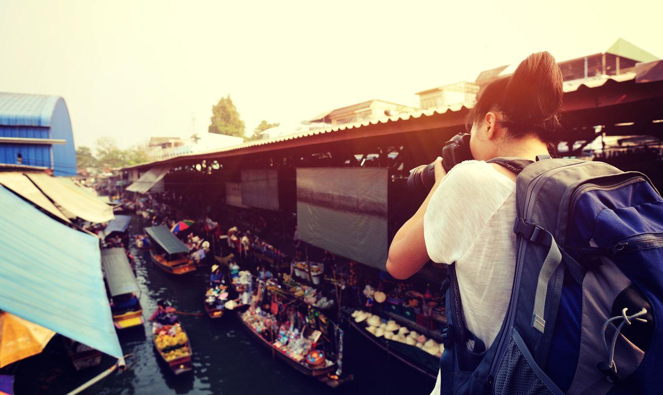 woman tourist taking photo at Damonen Saduak floating market,thailand