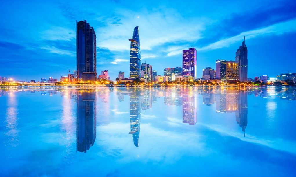 Reflection of Night view of Business District and Administrative Center of Ho Chi Minh city on Saigon riverbank.