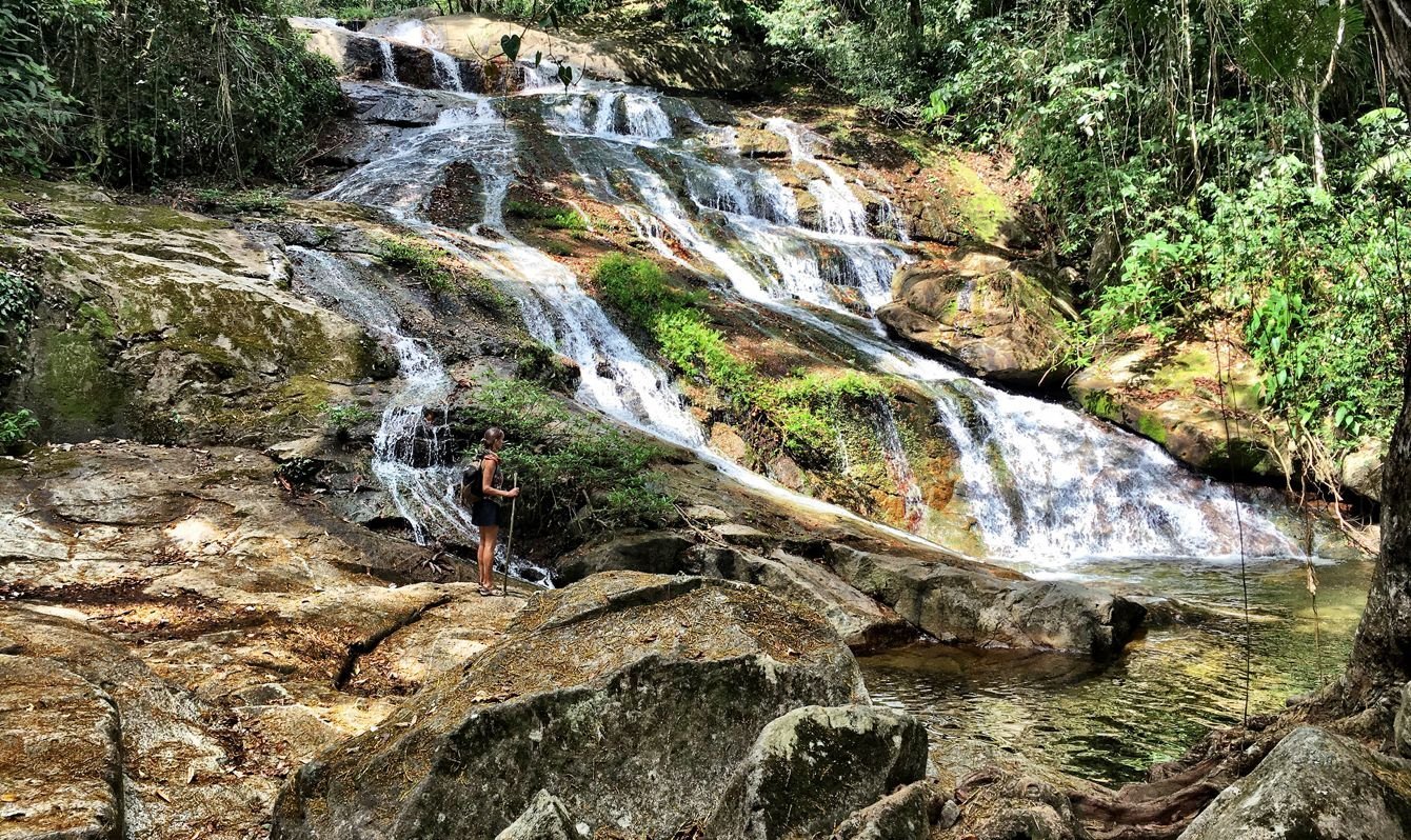 Hiker standing next to waterfall in Bocaina National Park. Belize, Central America.