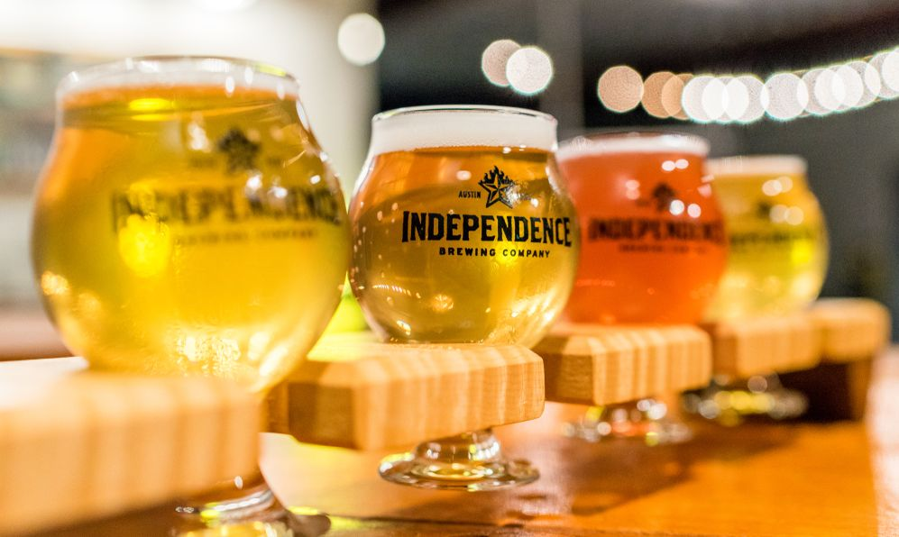 cold foamy beer flight and sampler is enjoyed in small pint glasses at the Independence Brewing Co. in Austin, Texas.