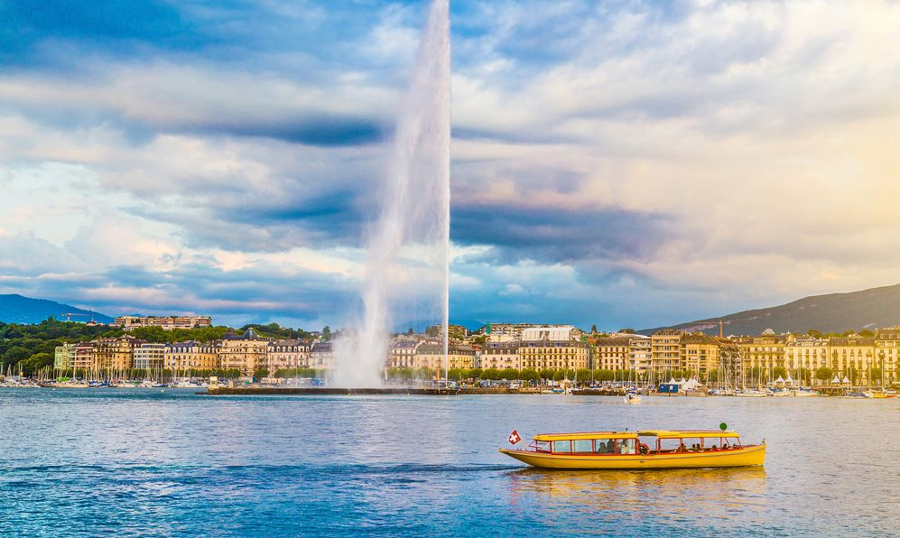 Panoramic view of Geneva skyline with famous Jet d'Eau fountain and traditional boat at harbor district in beautiful evening light at sunset
