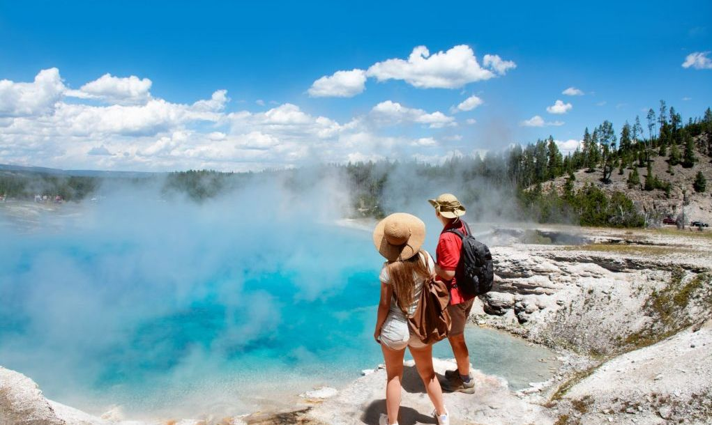 Man and woman with backpacks looking at Excelsior Geyser from the Midway Basin in Yellowstone National Park.