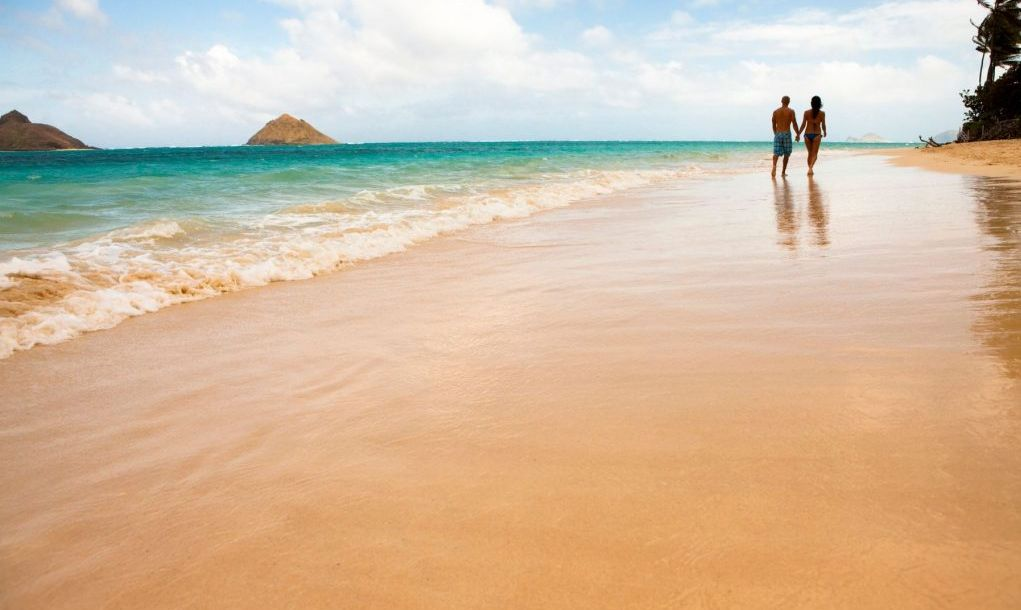 Couple walk along beach. Lanai Kai Beach, Oahu, Hawaii.