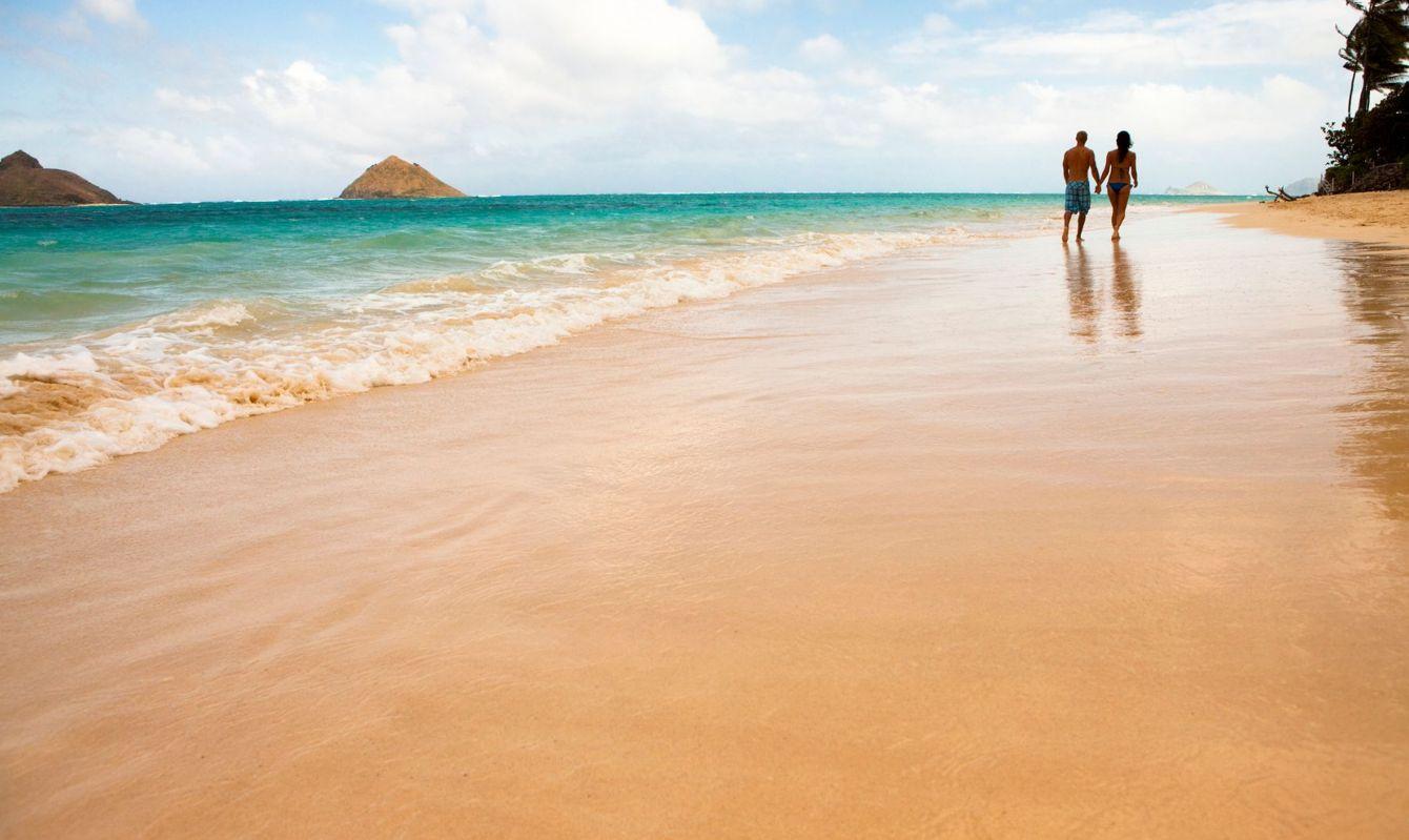 Couple walk along beach. Lanai Kai Beach, Oahu, Hawaii.