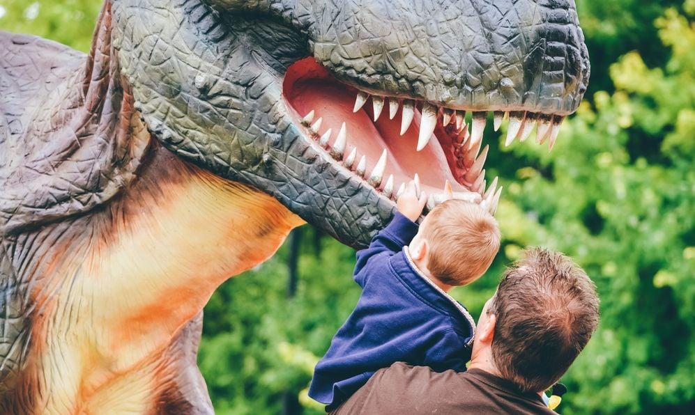 a child watches a dinosaur sculpture in amusement park Kings Island
