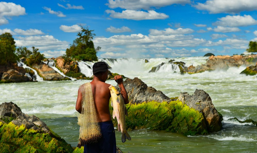Khone Phapheng Falls and fisherman on beautiful sky, Laos