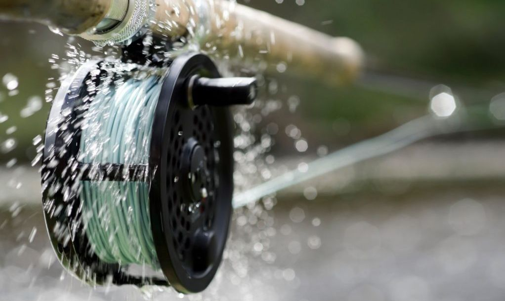 A fly fishing reel sends water flying as it spins at high speed while letting the line out fast.