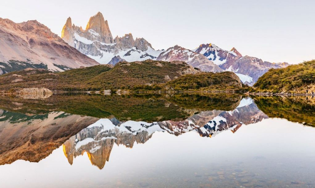 A view of Mount Fitz Roy reflected in a mirror calm Laguna Capri in Los Glaciares National Park above El Chalten