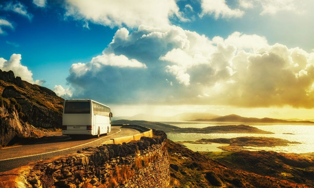 Tourist white bus on mountain road. Ring of Kerry, Ireland.