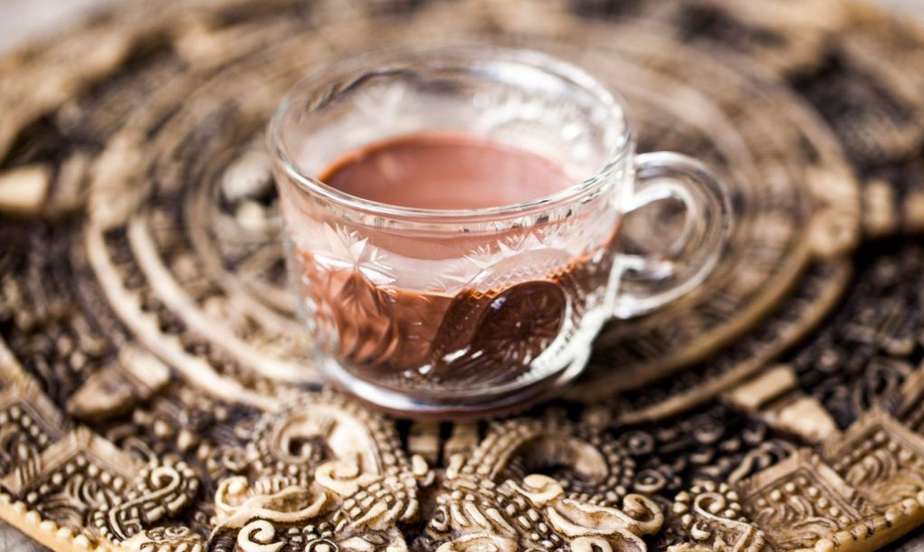 Ceremonial cacao drink (raw chocolate super food) on top of a mayan calendar