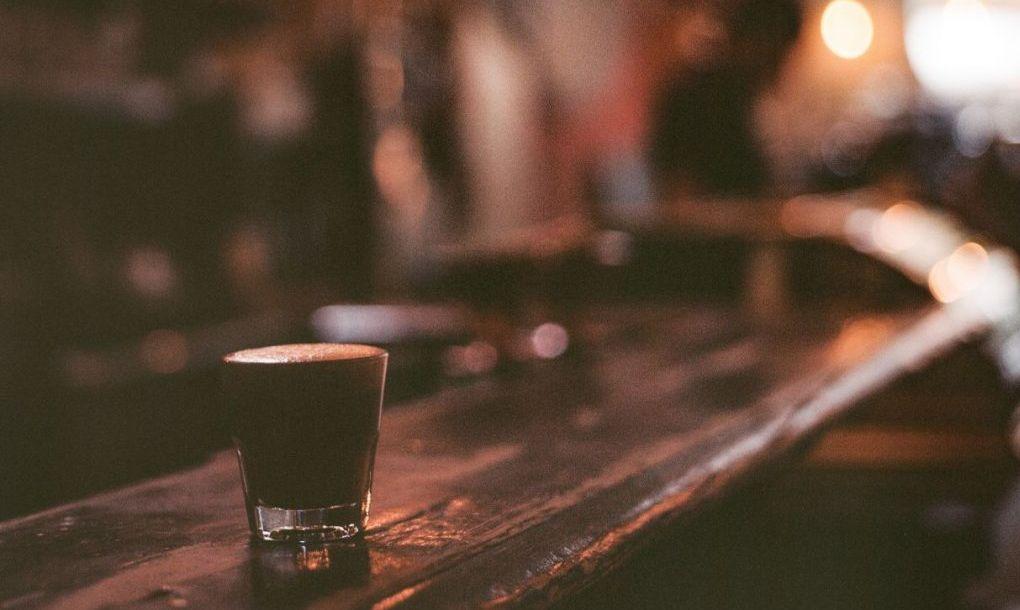 A drink sitting on a shelf at a bar