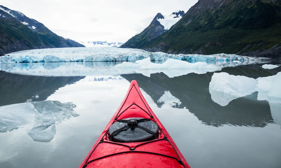 A red kayak floats among many icebergs calved from the Spencer Glacier in the distance