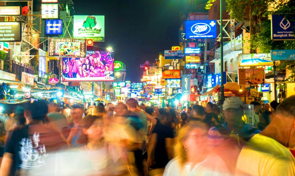iew from the middle of the famous Khao San Road as people pass by on the street in the night circa February 2018 in Bangkok, Thailand