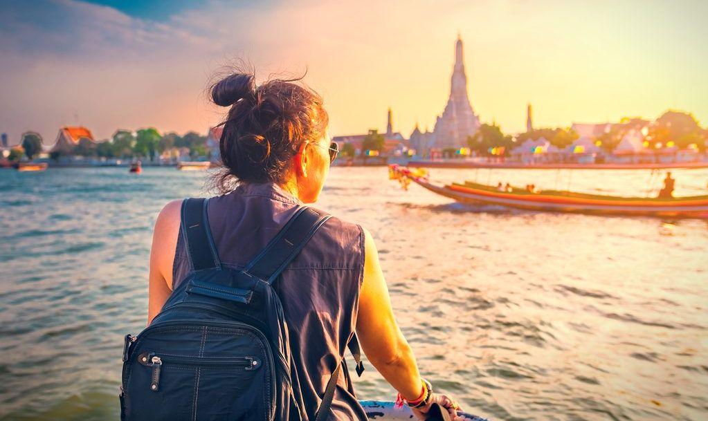 Traveler woman on boat joy view Wat Arun at sunset, Chao Phraya river