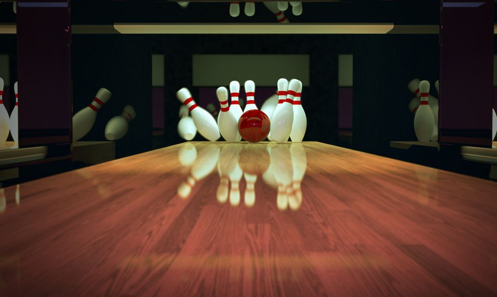 Red bowling ball is making a strike on wooden lane