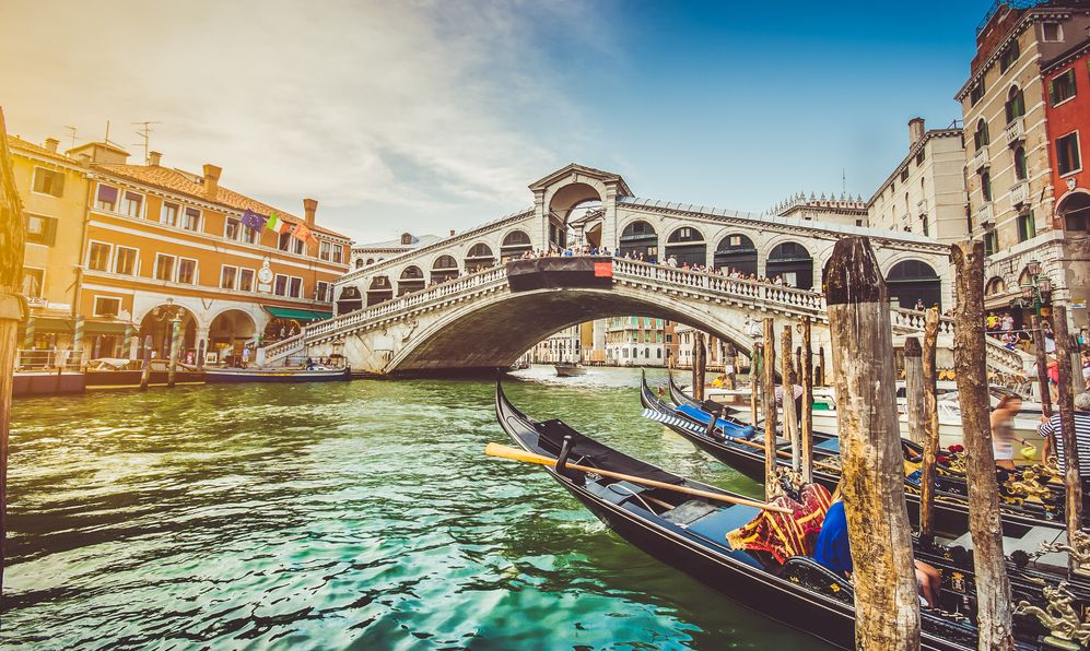 Panoramic view of famous Canal Grande with famous Rialto Bridge at sunset in Venice, Italy