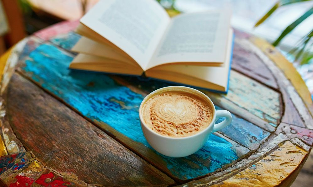 Cup of fresh coffee and book on a wooden table