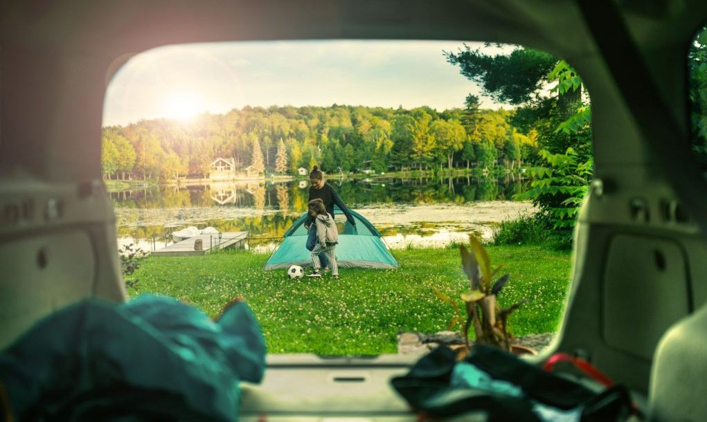 Mother and daughter playing soccer by the lake at their summer cottage in Quebec.View from the car. The camping tent is setup ready for the night