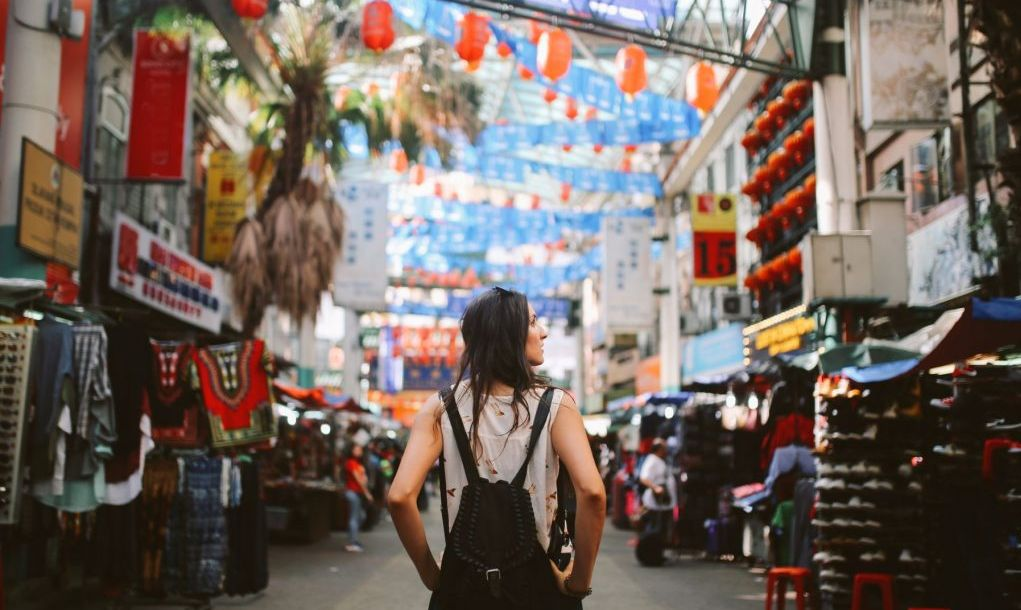 Young traveler woman walking through the stalls in Chinatown district of Kuala Lumpur, Malaysia.
