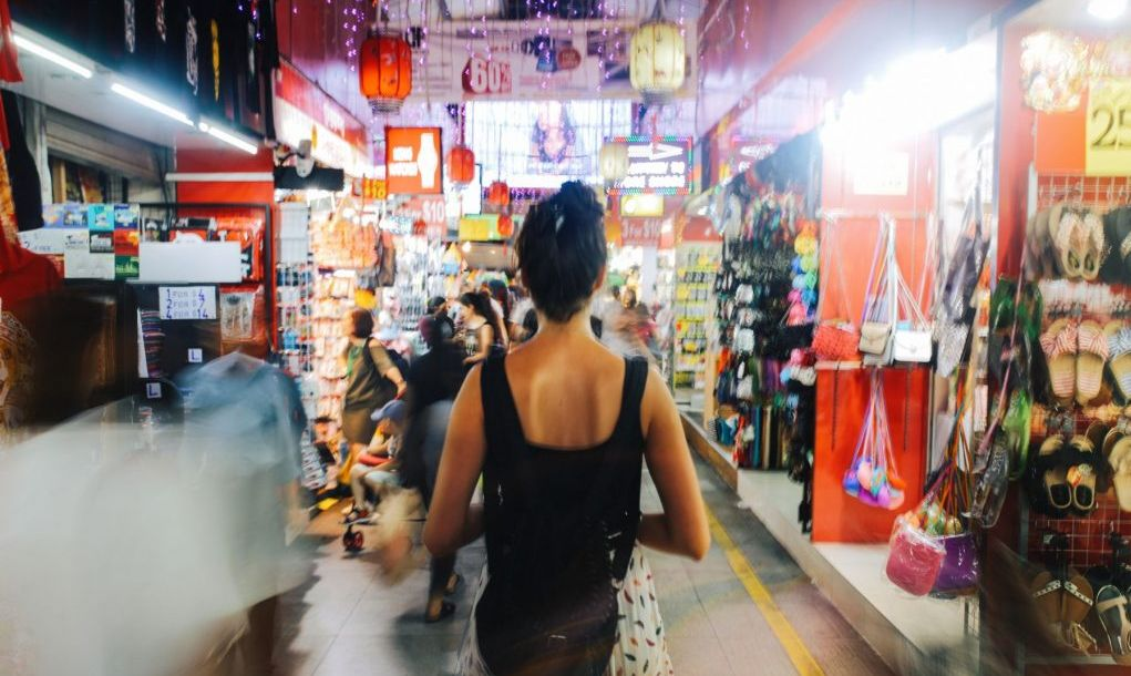 Young traveller woman walking through the small street markets in Singapore. She is carrying a backpack, strolling through the market stalls, looking for exotic and cheap stuff to buy, from technics and gadgets to delicious Asian street food.