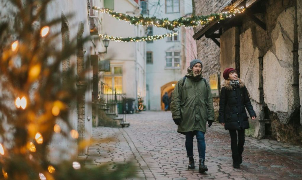 Japanese couple walking in Tallinn Old Town during Christmas