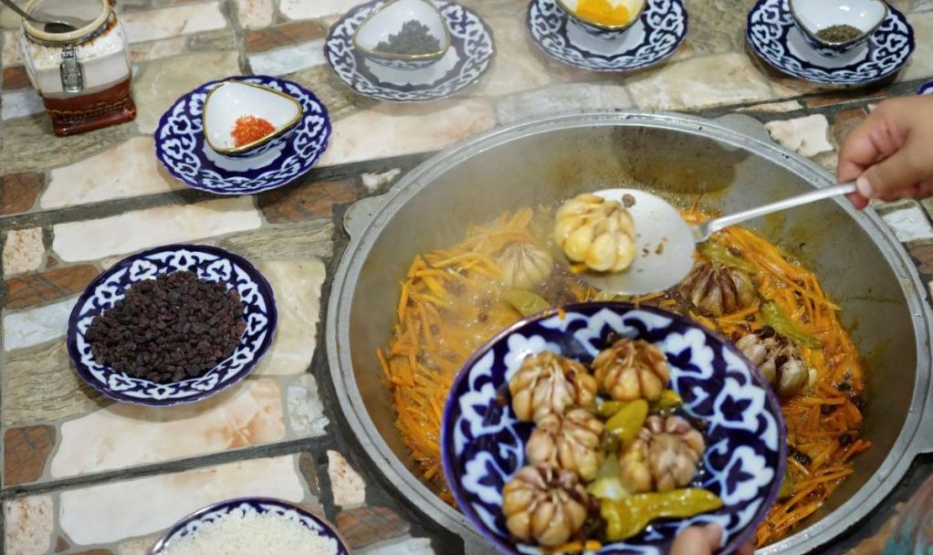 Traditional Uzbek way of preparing Lamb and Rice pilaf or Uzbek Plov in a covered kettle like wok surrounded with various spices as ingredients. Before putting the rice the cook takes garlic heads and pepper out as cooked.