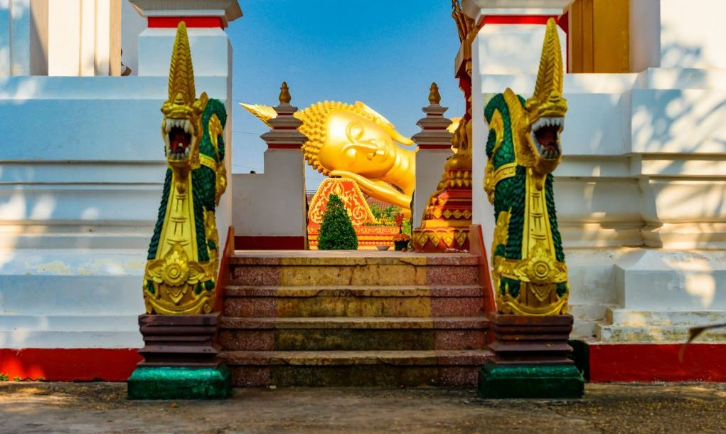 Stunning view of the reclining buddha statue in Pha That Luang complex. Pha That Luang is a Buddhist Temples complex in the centre of the city of Vientiane, Laos.