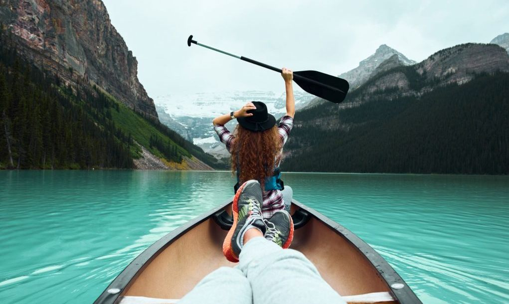 Shoot of young woman traveller on canoe enjoying nature views