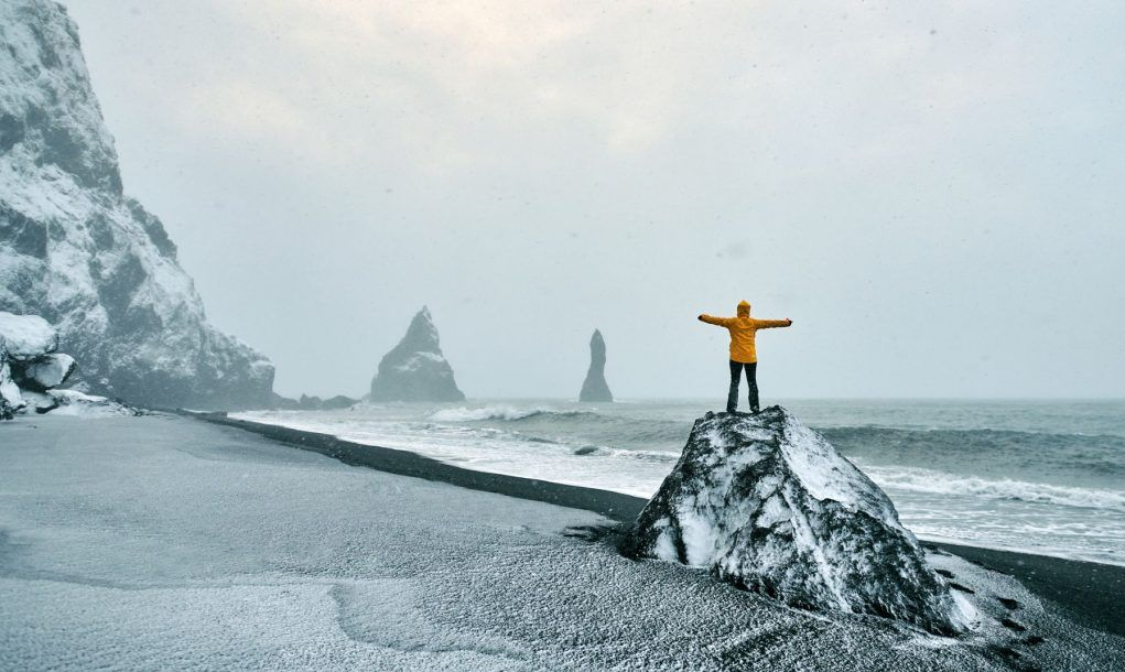 rear view of hiker woman on rock on Reynisdrangar beach in Iceland enjoying freedom.