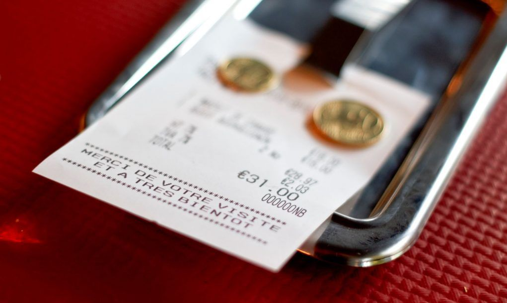 European (french) restaurant check with few tip coins left on it. Red paper napkin background, selective focus