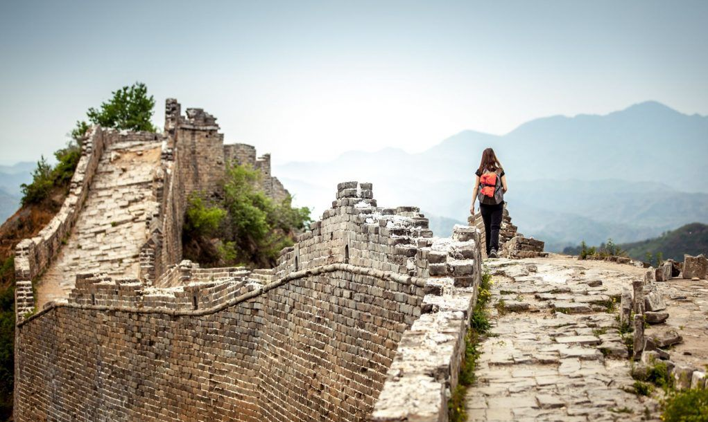Solo Woman Tourist at walking on the Great Wall Of China. She is wearing a backpack.