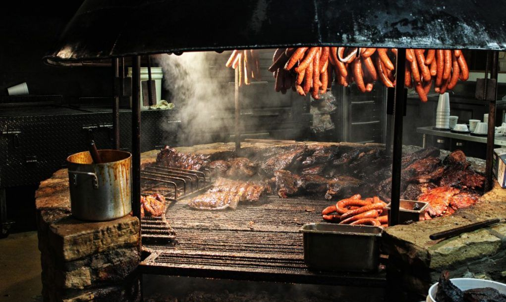 Sausages hanging over brisket smoking over a large BBQ pit.