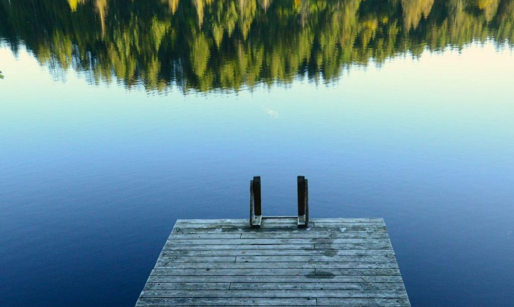A lonely dock on a calm lake. Jump in!