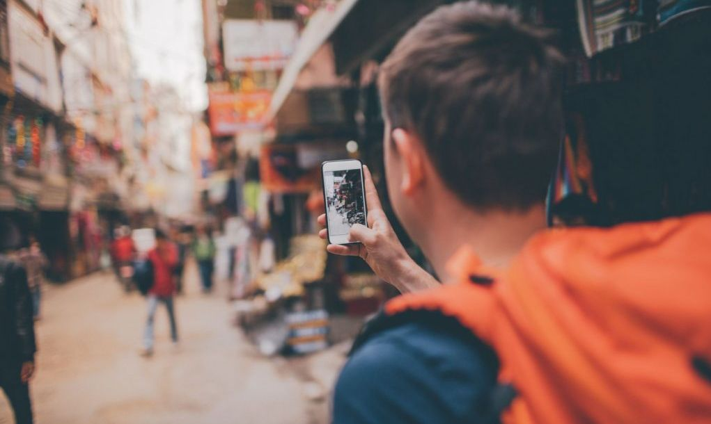 Photo of a tourist, travelling by foot and eager to learn about local lifestyle. He is capturing rememberable moments on his mobile phone.