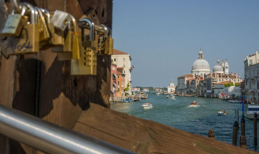 Church Santa Maria della Salute seen through the bridge with love locks, Ponte dell Accademia, Venice, and church Santa Maria della Salute