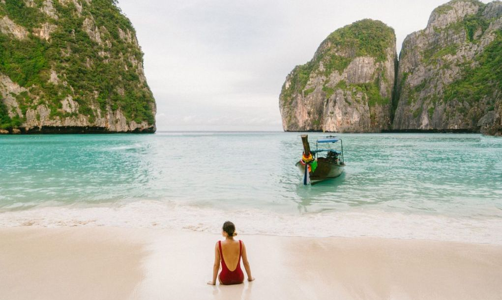 Young Caucasian woman sitting on Maya Bay beach in Krabi, Thailand