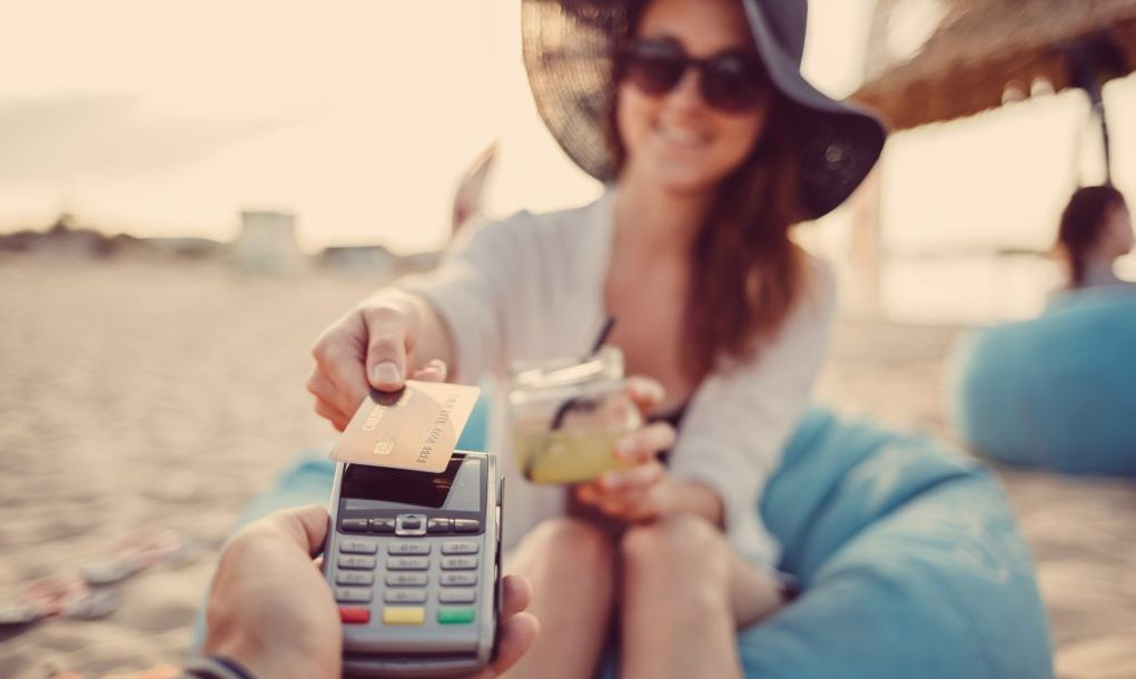 Woman on the beach making contactless credit card payment