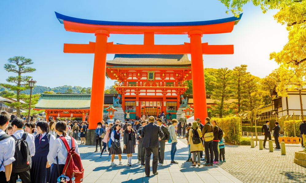 Red Torii gates at Fushimi Inari Taisha with tourists and Japanese students. Fushimi Inari is the most important Shinto sanctuary.