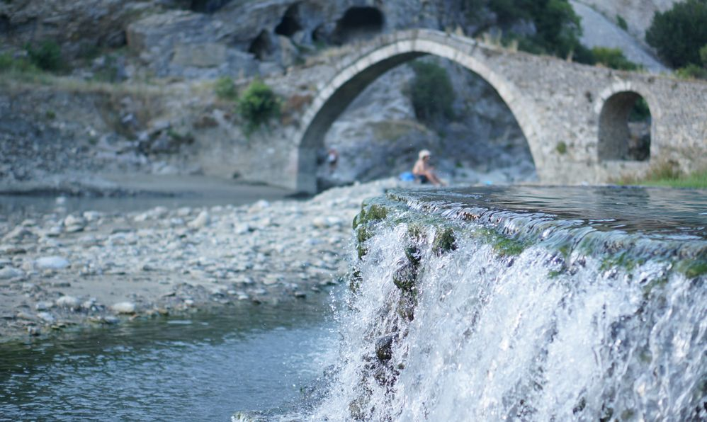 Beautiful shot of water falling out of a men made stone bath with an unfocused arched stone bridge in the background. Permet, Albania