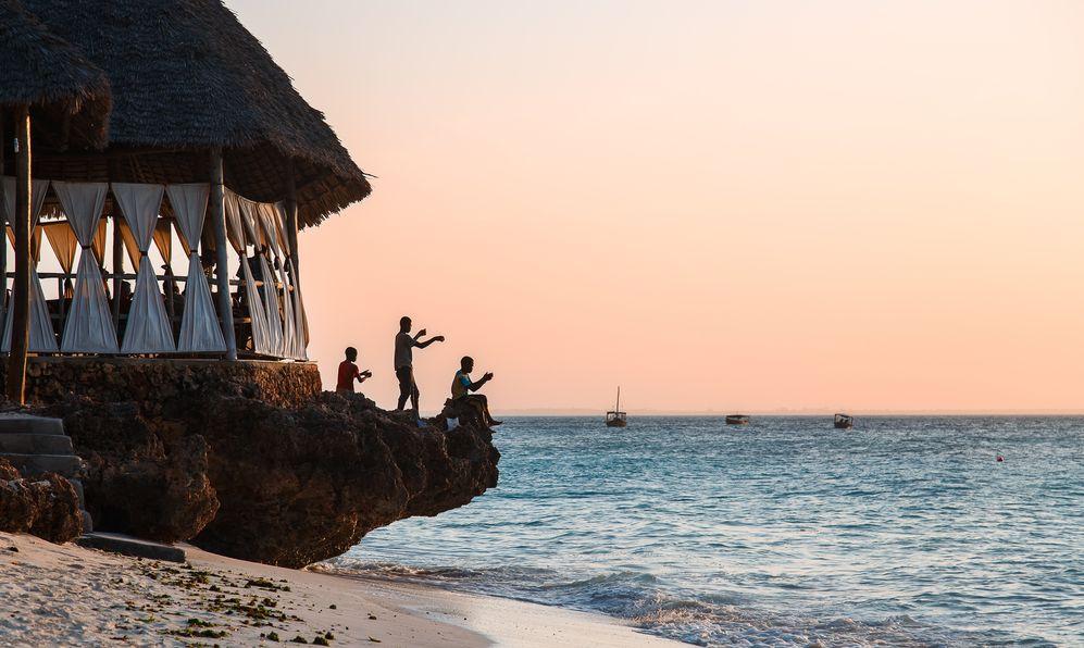 Boys fishing at sunset on the rock on the ocean, Nungwi, Kendwa, Zanzibar island, Tanzania