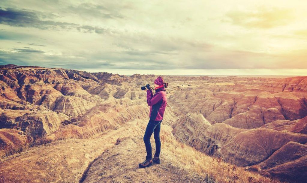 Vintage toned photo of a female photographer taking pictures at sunset, Badlands National Park, South Dakota, USA.