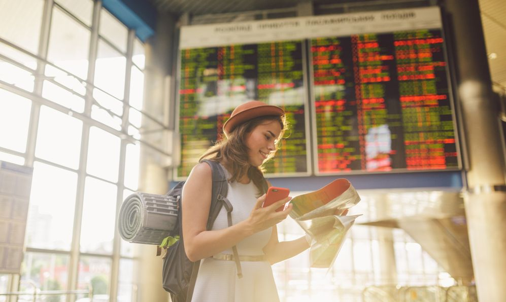 young caucasian woman in dress and backpack standing inside train station terminal looking at electronic scoreboard holding phone, map paper hand navigation