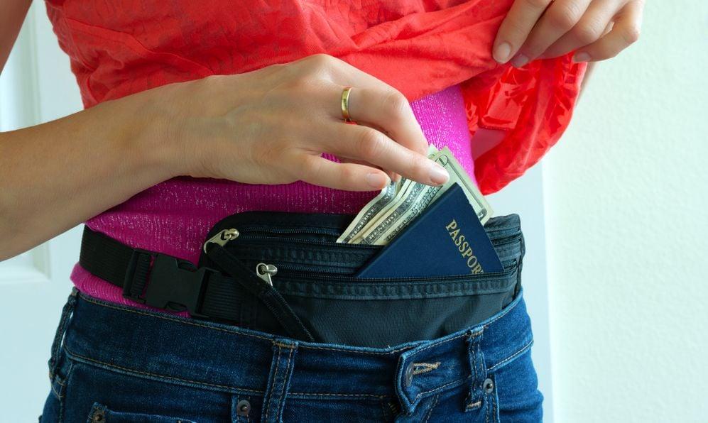 Woman getting cash and passport from hidden travel money belt