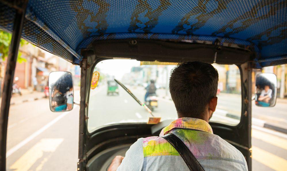 Tuk-tuk driver on road of Sri Lanka, view from ca