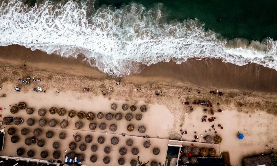 A drone view of rows of palapas on the beach looking out on Banderas Bay