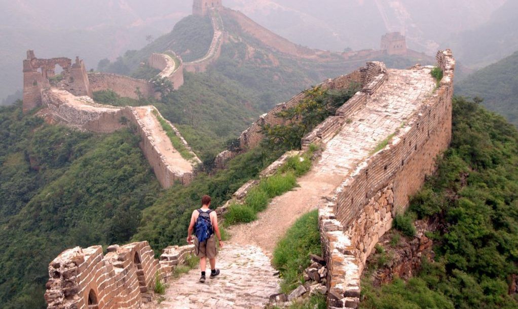 A young man hikes alone along the Great Wall of China. This section is between Jinshanling and Simatai.