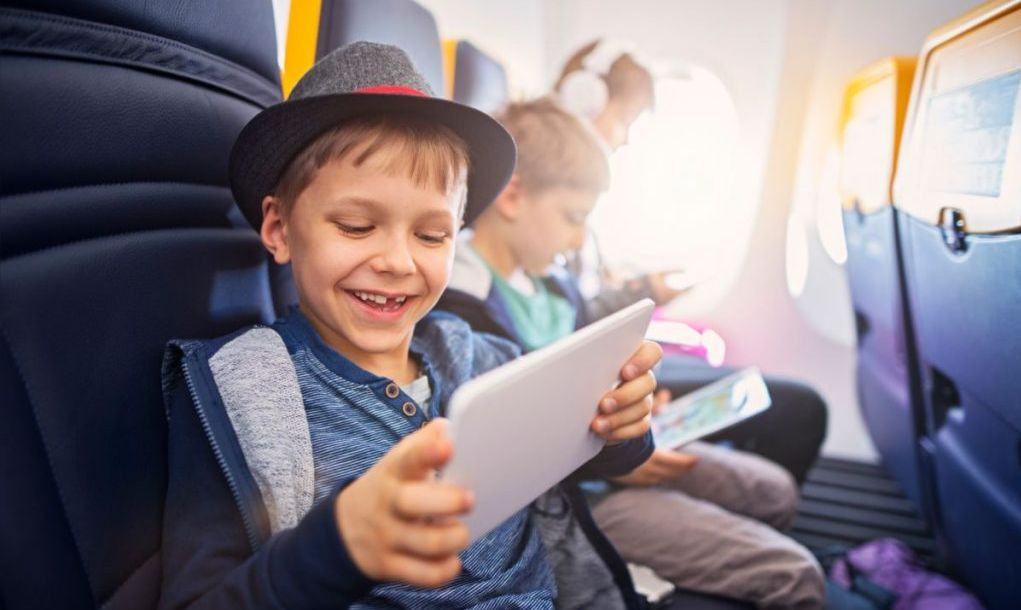 Happy kids travelling in plane. The kids are using technology to make the flight even more fun.
