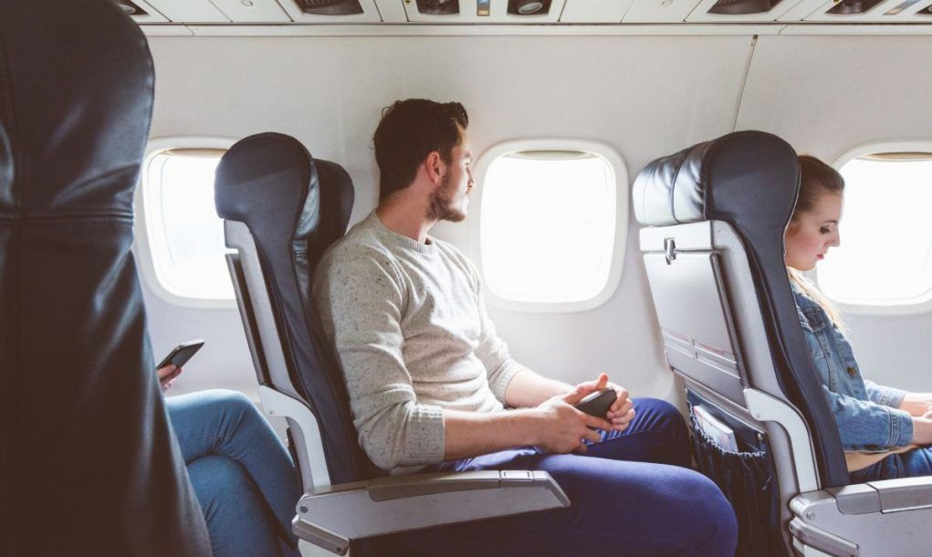 Young man sitting in airplane cabin near window. People flying by plane.
